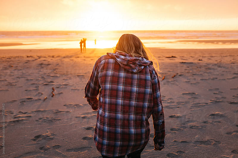 young female walks toward group of friend during sunset on beach by Jesse Morrow for Stocksy United