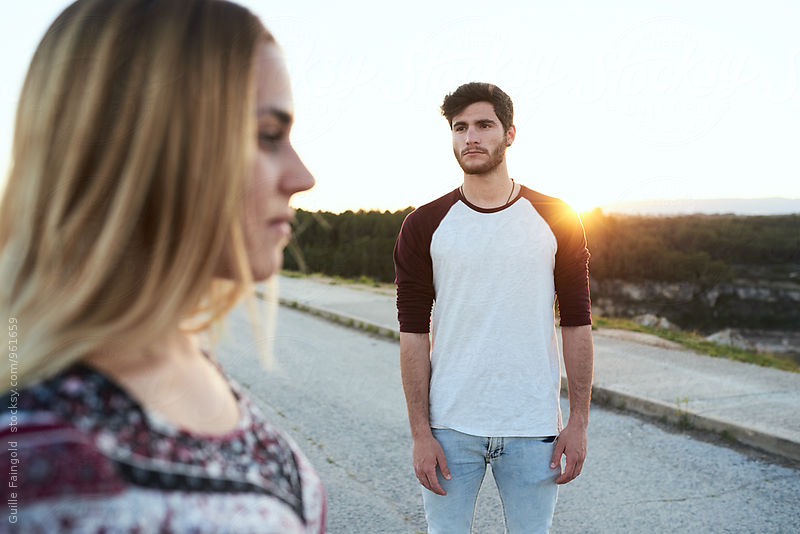 Couple on road against of sunset by Guille Faingold for Stocksy United