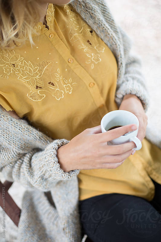 Woman holding a cup of coffee with a wellow shirt in the morning by Lydia Cazorla for Stocksy United