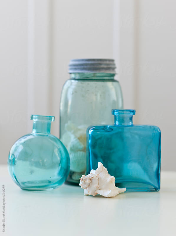 Glass bottles and shell by Daniel Hurst for Stocksy United