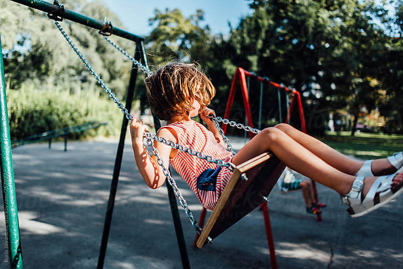 Girl swinging on the swing in the park by Boris Jovanovic for Stocksy United