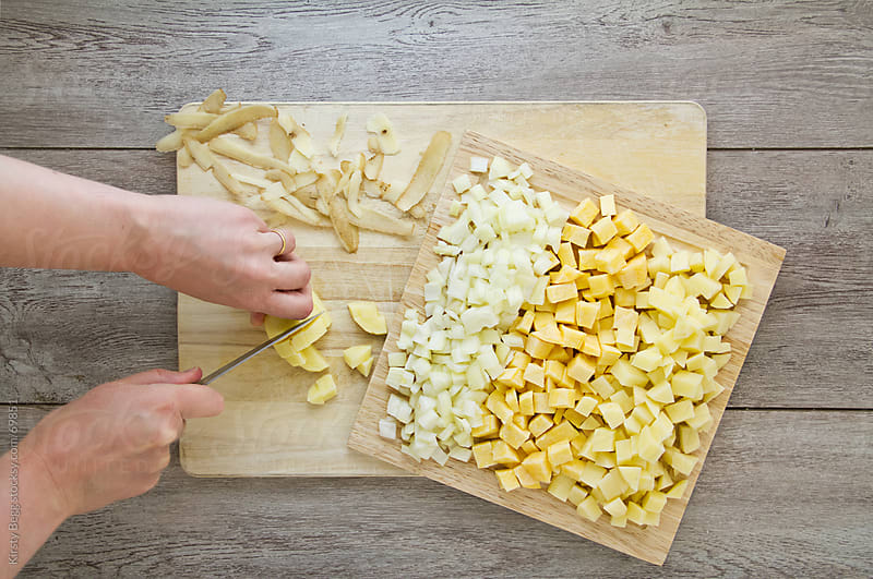 Dicing vegetables (onion, swede, potato) for Cornish Pasties (hand pies) by Kirsty Begg for Stocksy United