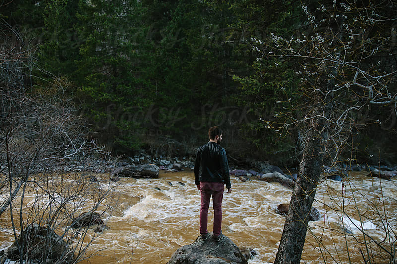 Man standing near rapid mountain river by Andrey Pavlov for Stocksy United