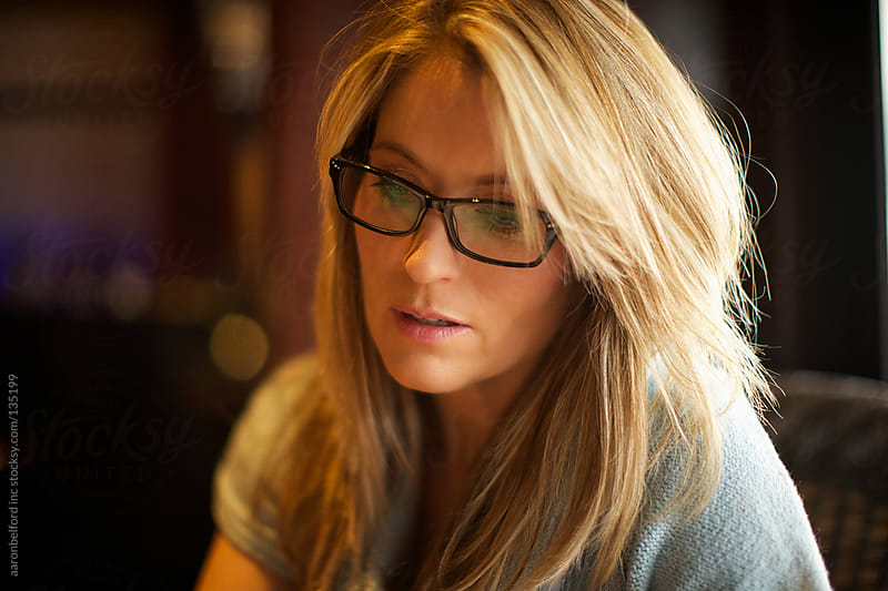 Woman reads with glasses on by aaronbelford inc for Stocksy United