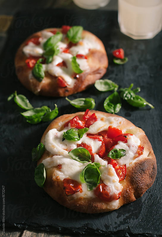 Italian focaccia with tomato, mozzarella and basil by Davide Illini for Stocksy United