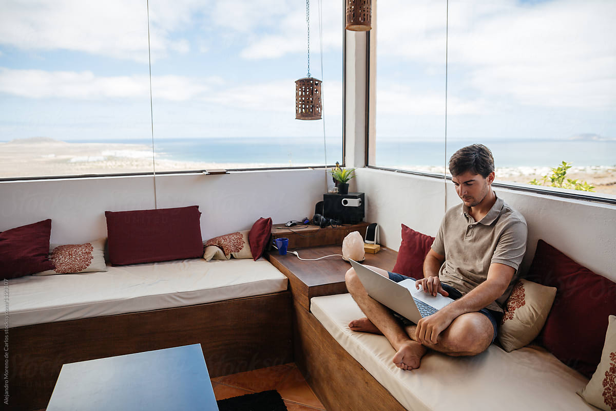 Man Using Laptop Sitting On Sofa And Working At Luxury Home With Scenic  Views Out Of