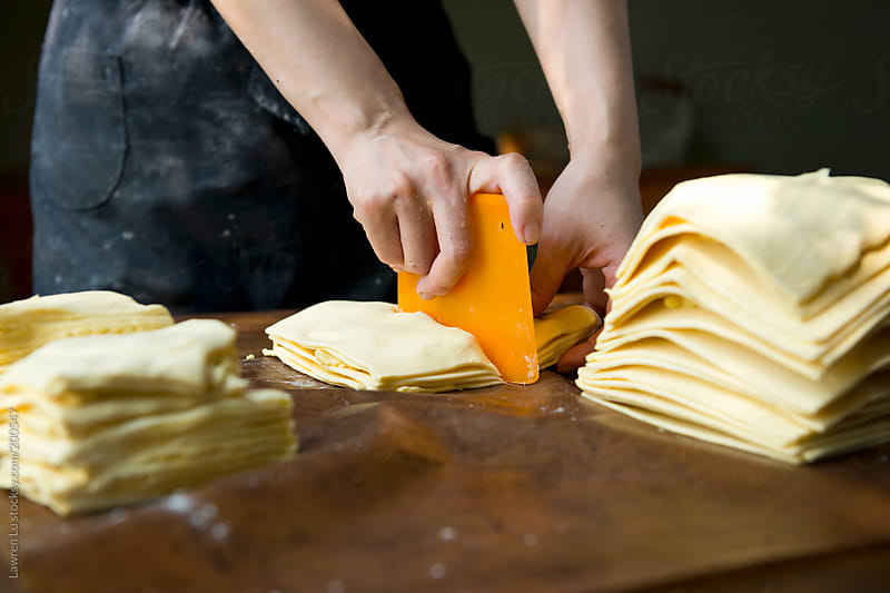 Woman hands cutting puff pastry by Lawren Lu for Stocksy United