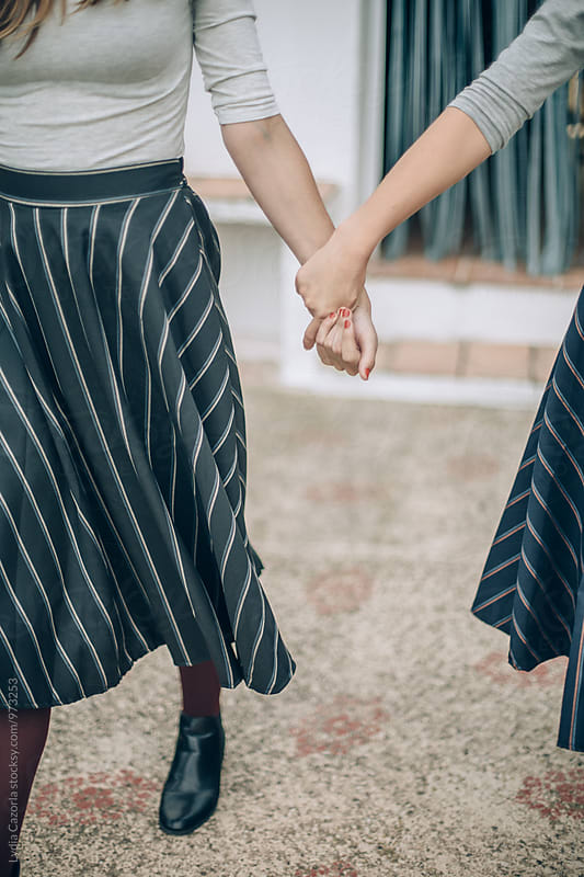 Two friends womans holding hands by Lydia Cazorla for Stocksy United