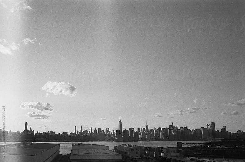 The black and white film photo of view to Manhattan from Brooklyn by Anna Malgina for Stocksy United
