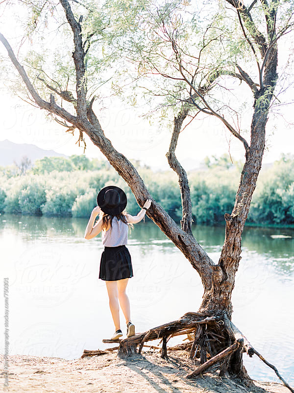 Woman standing on tree along river by Daniel Kim Photography for Stocksy United