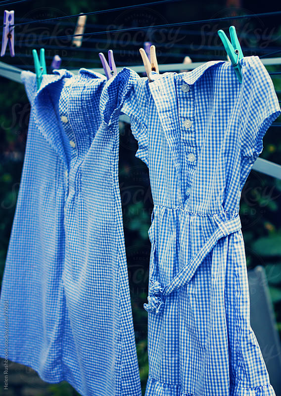School dresses hanging on a washing line by Helen Rushbrook for Stocksy United