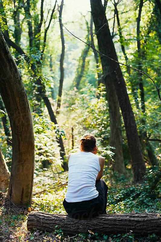 Woman sitting on a log in forest by Aleksandra Kovac for Stocksy United