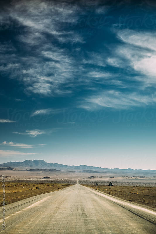 Long straight empty desert road leading into the horizon by Micky Wiswedel for Stocksy United