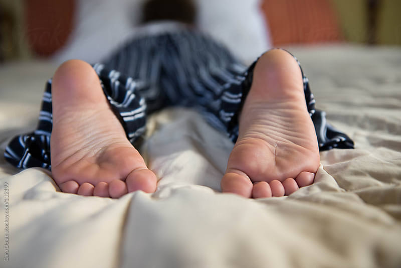 Child's feet and toes as he lies on his bed by Cara Dolan for Stocksy United