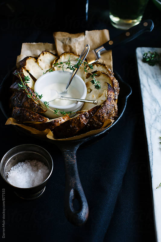 Side dish: Roasted celeriac wedges with thyme and yogurt dressing on a black background. by Darren Muir for Stocksy United