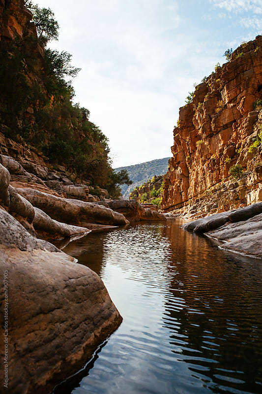 View on moroccan canyon with river in sunlight by Alejandro Moreno de Carlos for Stocksy United