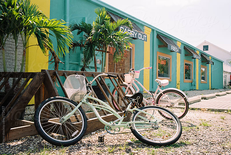 Two colorful bicycles parked outside of a restaurant in a seaside town by Joey Pasco for Stocksy United
