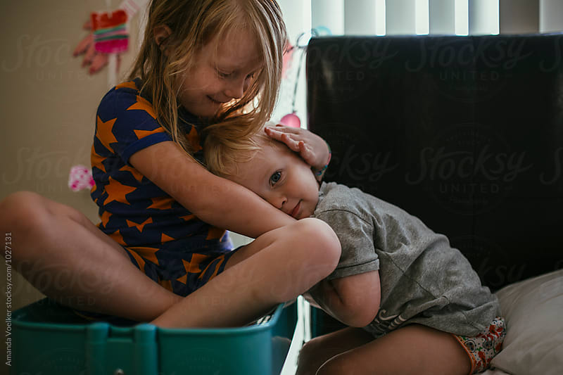 A big sister Cradles her Toddler brother's head on her lap by Amanda Voelker for Stocksy United
