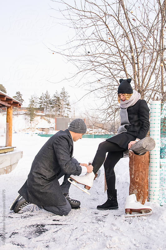 Young man helping his girlfriend to tie her skates by Danil Nevsky for Stocksy United