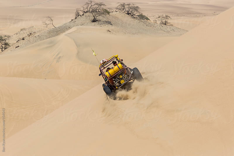 Dune buggy with passengers speeding across the side of a large d by Ben Ryan for Stocksy United