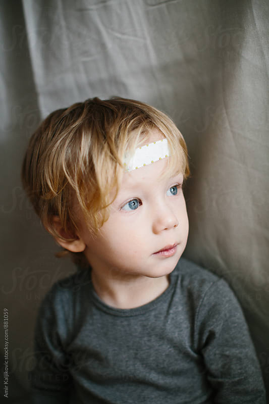 Little boy wearing a plaster on his forehead by Amir Kaljikovic for Stocksy United