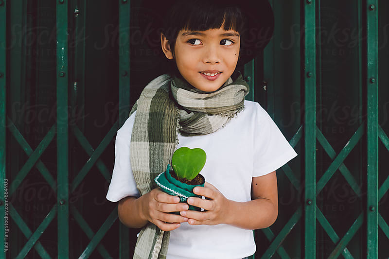 Cute Asian boy in valentine's day holding plant pot by Nabi Tang for Stocksy United