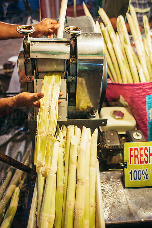 Man squeezing fresh sugar cane juice through a machine  by Jovo Jovanovic for Stocksy United