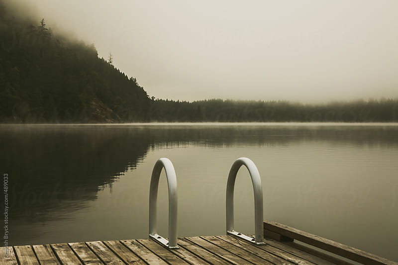 Empty dock at the calm lake. by Cherish Bryck for Stocksy United