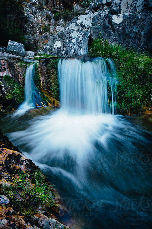 long exposure of a small waterfall in a rocky mountain stream by Micky Wiswedel for Stocksy United