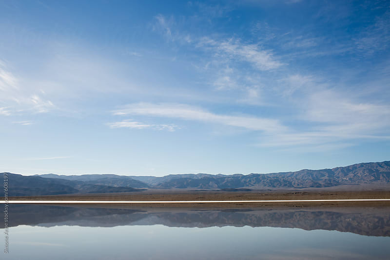 Blue sky reflections in salt lake by Simone Anne for Stocksy United