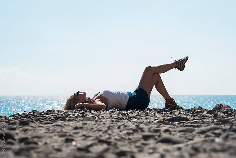 Woman relaxing and lying on the cliff against the sea by Simone Becchetti for Stocksy United