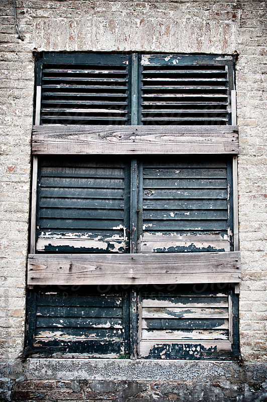Window damaged, blocked with wooden boards by Jean-Claude Manfredi for Stocksy United