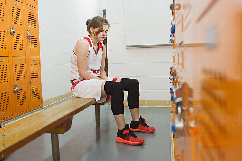 female basketball player sits quietly on bench in locker room by Tana Teel for Stocksy United