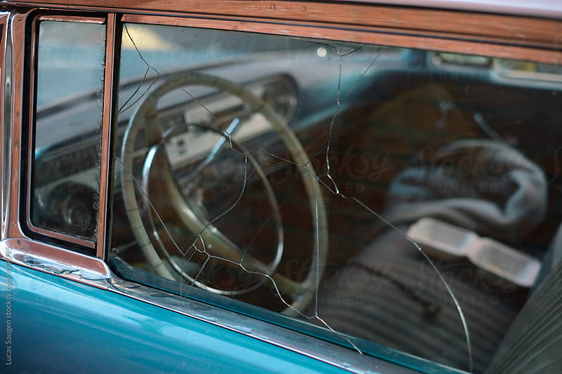 Looking into an old car with a broken drivers window. by Lucas Saugen for Stocksy United