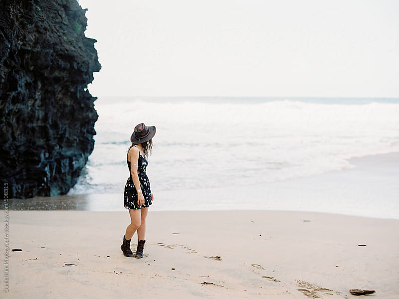 Woman walking on beach by Daniel Kim Photography for Stocksy United