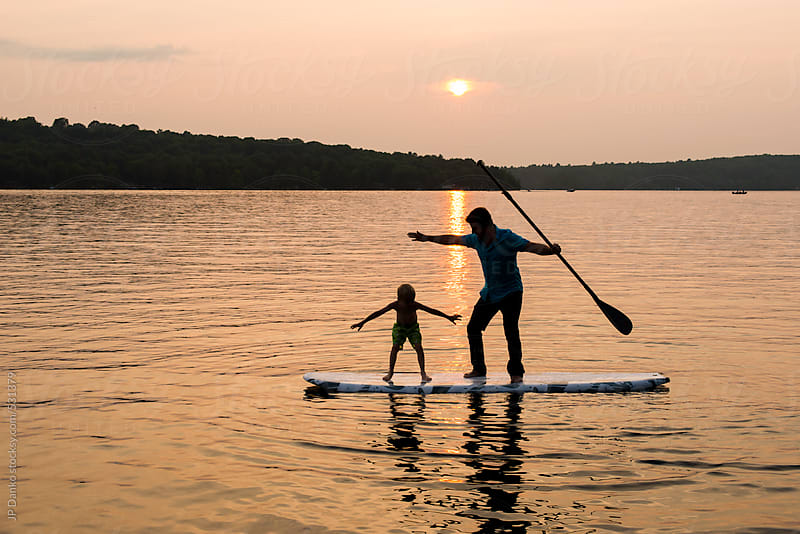 Silhouette of Man and Boy Playing on Stand Up Paddle Board on Lake by JP Danko for Stocksy United