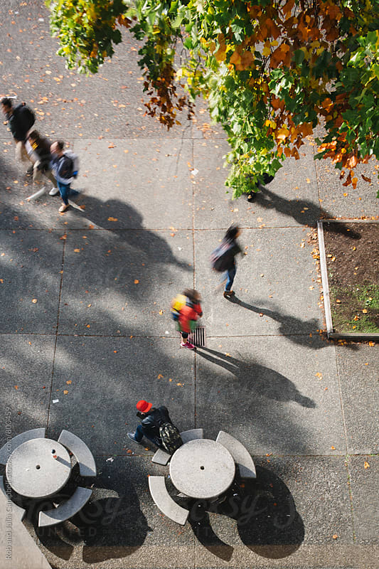 top down view of people walking through courtyard by Rob and Julia Campbell for Stocksy United
