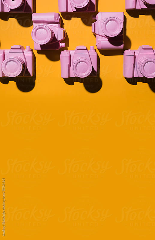 Pink cameras arranged on orange/yellow background. by Marko Milanovic for Stocksy United