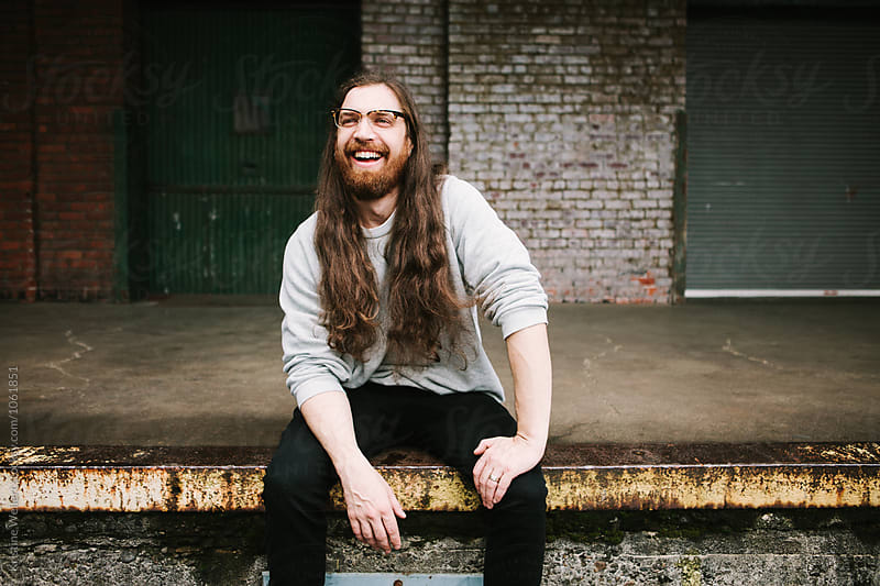 Smiling Man sitting on a loading dock with a brick wall behind him by Kristine Weilert for Stocksy United