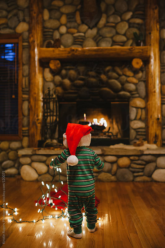 Toddler boy playing with Christmas lights near fireplace by Kristin Rogers Photography for Stocksy United
