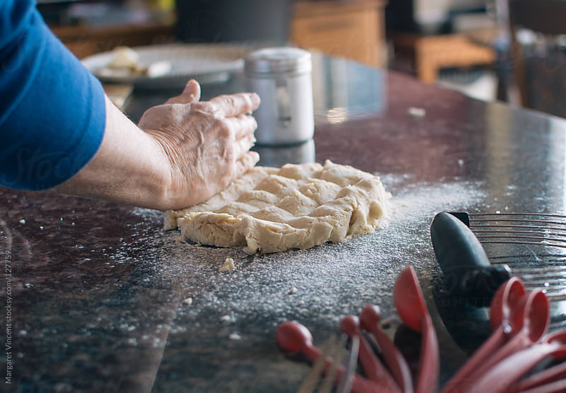 woman pats dough while baking by Margaret Vincent for Stocksy United