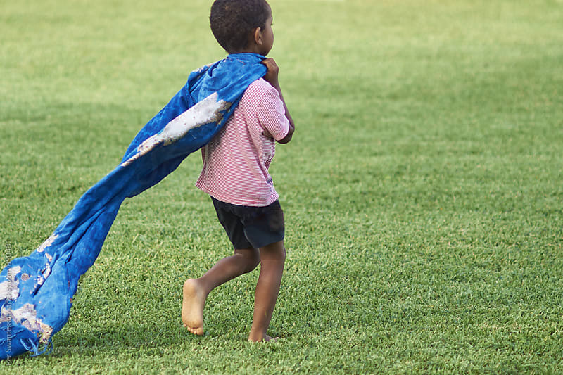 Young kid playing with a blue cape  by Per Swantesson for Stocksy United