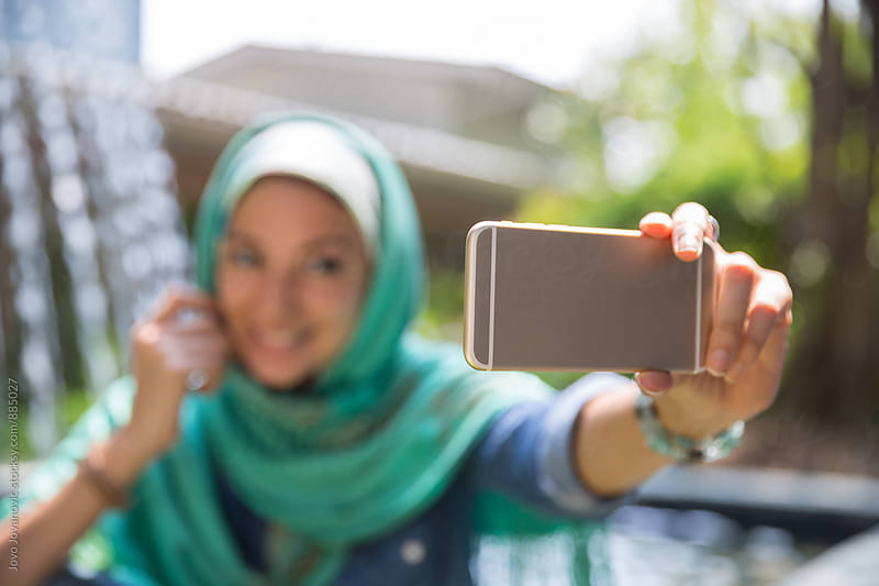 Woman wearing hijab taking a selfie  by Jovo Jovanovic for Stocksy United