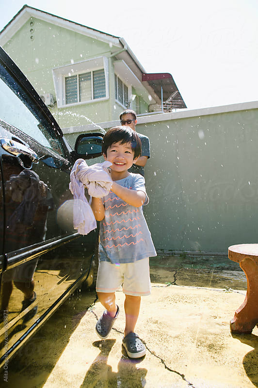 Little boy helping dad washing car by Alita Ong for Stocksy United