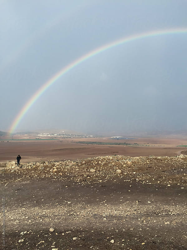Man walking away from rainbow in a rural biblical landscape by Lior + Lone for Stocksy United