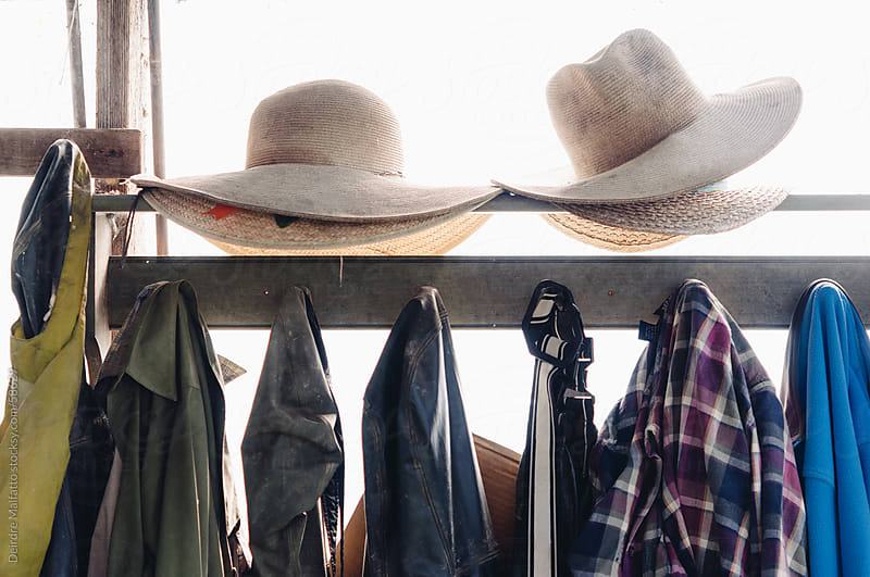 Waterproof Overalls, Jackets, and Straw Hats on Farm by Deirdre Malfatto for Stocksy United