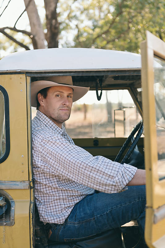 farmer in his truck by Gillian Vann for Stocksy United