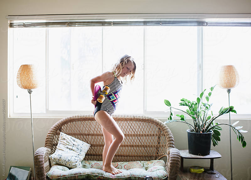Young girl holding skateboard standing on couch in apartment by Kristin Rogers Photography for Stocksy United