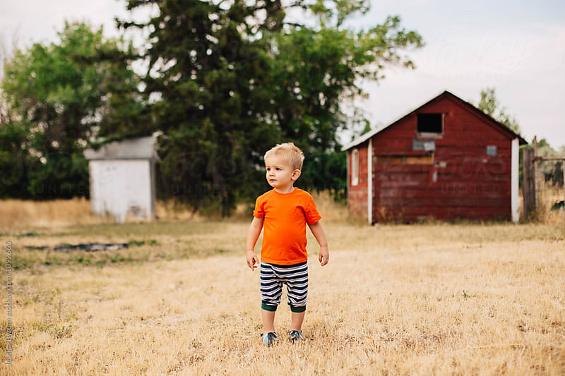 Cute toddler boy standing outside on a farm in the morning. by Jessica Byrum for Stocksy United