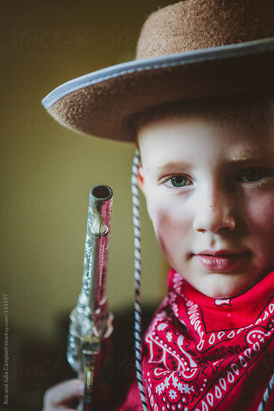 Young boy dressed up like a cowboy with hat, gun and bandana by Rob and Julia Campbell for Stocksy United